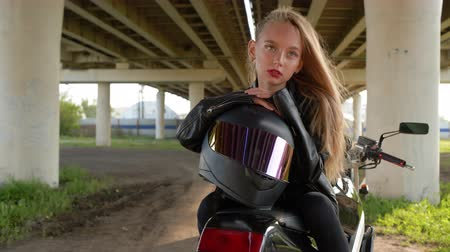 korhadt : Biker girl with moto helmet sitting on motorcycle under car bridge in city. Moto girl in black leather jacket posing on motorbike on urban landscape
