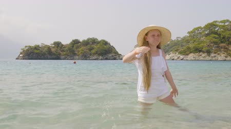 grimacing : Funny girl posing in sea. Adorable teenage girl in wide-brimmed hat standing in calm blue sea, grimacing and gesturing at summer day.