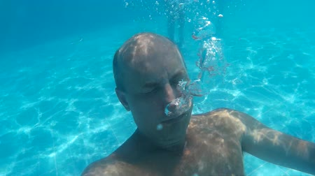 fejest ugrik : Bald man diving underwater swimming pool and blowing air bubble. Underwater view man blowing air bubble in transparent blue water pool in resort