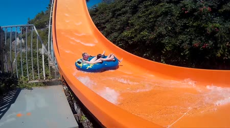 waterslide : Girls sliding on water slide in amusement aquapark at summer vacation. People having fun riding on slides in outdoor water park at holiday Stock Footage