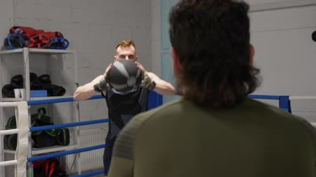 each other : Sportsman training throw medicine ball on boxing ring in fight club. Boxers man throwing ball to each other on warming training in sport club. Cardio exercise in gym Stock Footage