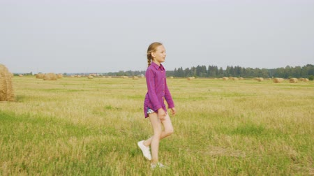 kleine meisjes : Smiling girl walking on field. Adorable cheerful child in checkered shirt and denim shorts walking on autumn field with haystacks. Rural country concept Stockvideo