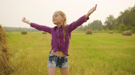 stoupat : Happy child on field. Adorable cheerful preteen girl in checkered shirt and denim shorts standing with open arms on field with haystacks. Beauty in nature concept Dostupné videozáznamy