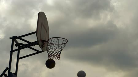 bolas : Person playing basketball. Cropped shot of human hand throwing ball into hoop against cloudy day. Sport concept Vídeos