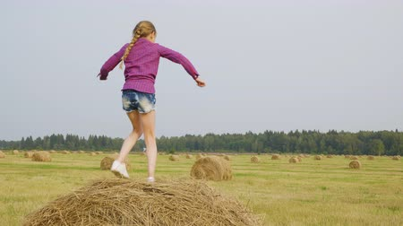brim : Happy child dancing on haystack. Adorable cheerful pretten girl in checkered shirt and denim shorts dancing on hay in autumn field. Harvest concept