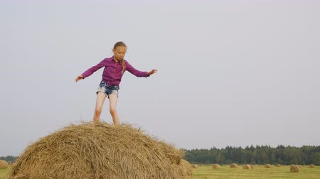palheiro : Children playing on haystack. Cute happy girl dancing and jumping on haystack while cheerful boy running on field. Childhood concept Stock Footage