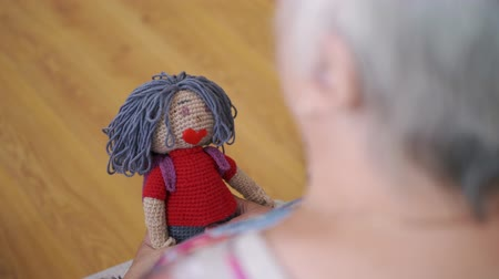 долл : Hands elderly woman holding handicraft knitted doll. Close up old grandmother hands holding handmade doll