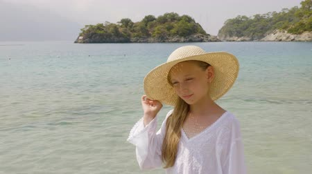sunhat : Portrait cute girl in straw hat on paradise beach. Teenager girl squinting on sunny day at summer beach. Young model posing on sea beach Stock Footage