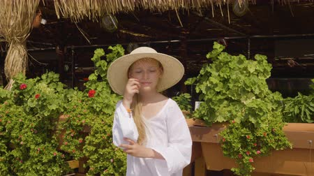 sombrero de paja : Playful teenager girl dancing front camera on summer plants background. Young girl in straw hut showing dance on summer terrace background in resort hotel
