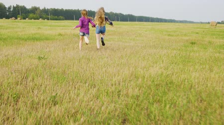 palheiro : Two girl teenagers running on countryside field on hay stack background. Cheerful girls running on countryside field in autumn village rear view