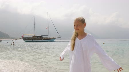 bílé mraky : Cute girl teenager in white tunic with enjoying sea on ship landscape. Tourist girl standing on summer sea on mountain silhouette and clouds background