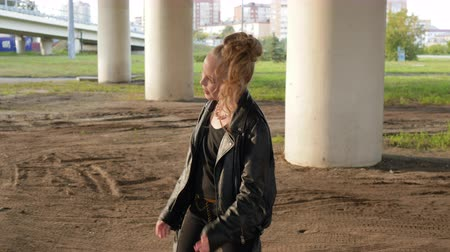 serseri : Punk girl dancing on street. Cute smiling teenage girl in leather jacket with bright makeup and hairstyle walking and dancing under urban bridge.