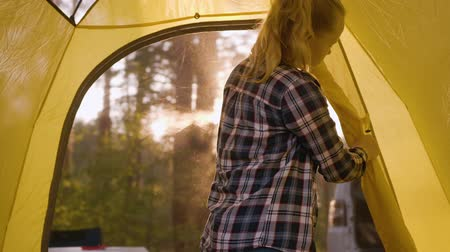 beállítás : Teenager girl opening window camping tent in sunny forest. Young tourist girl inside yellow camping tent in forest hike. Summer tourism in forest. Morning sunrise or evening suset