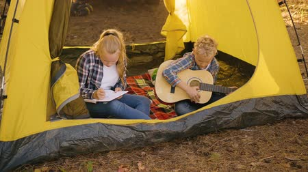 akusztikus : Teenager boy with guitar sitting in camping tent. Young girl teenager painting or write song inside tourist tent in forest campsite. Boy play guitar. Teenagers in forest camping at summer vacation
