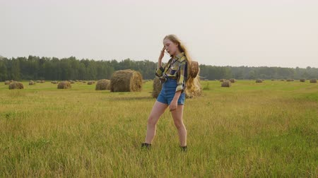 bales : Country girl in checkered shirt and jeans short posing on country field in farmland. Cowboy girl on haystack background on harvesting field in autumn village Stock Footage