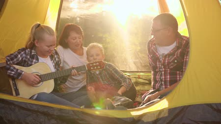 sonnenschein : Happy family singing song by guitar in camping tent on sunlight background. Tourist family having fun in camping. Funny girl playing guitar on forest hike. Backlit sunflare Videos