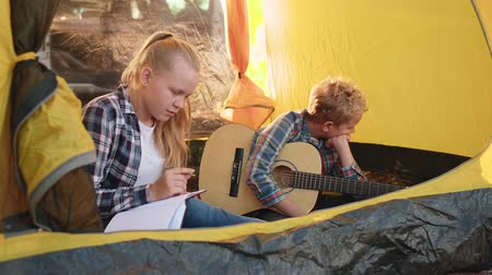 kytara : Teenager girl and boy with guitar sitting inside camping tent in forest. Girl teenager thinking about note in notebook. Boy relaxing with guitar in tourist tent in summer hike