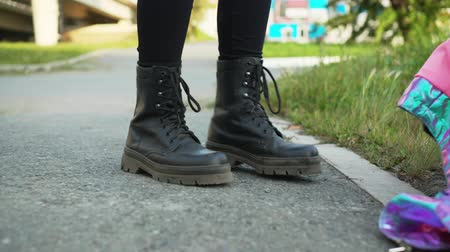 buty : Female legs wearing black leather boots standing on asphalt road at summer. Girl in leather shoes walking on green grass in city park Wideo