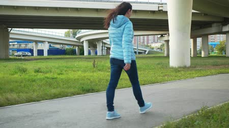 perfil : Young woman in jeans and blue jacket walking in modern city on highway background. Back view woman walking on urban background. Brunette woman going on city street on freeway landscape