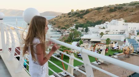 veranda : Teenager girl standing on outdoor terrace with sea and mountain view. Tourist girl enjoying sea landscape from appartment balcony. Girl resting in summer vacation Dostupné videozáznamy