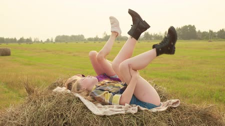 bales : Girl teenager lying on haystack and swaying legs up. Happy teenager girls moving legs on autumn haystack. Girl friends relaxing on hay stack at harvesting field