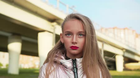dospívání : Portrait teenager girl with bright makeup lips and eyes on car bridge background. Face blonde teenager girl with long hair waving on wind on urban landscape Dostupné videozáznamy