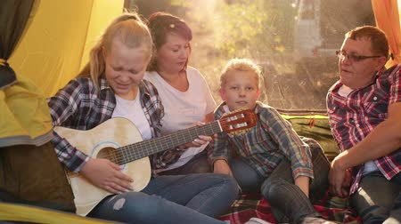 acoustical : Tourist family singing song by guitar in camping tent in forest hike. Friendly family singing song at camping on sunshine background. Teenager girl playing guitar for family