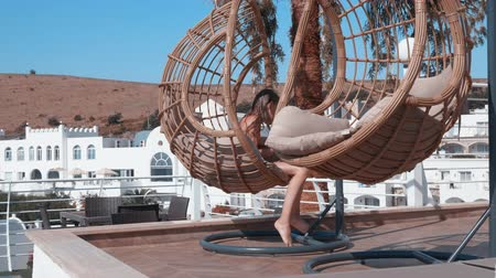 ülés : Cheerful girl relaxing in hanging chair with mobile phone in resort hotel. Young girl teenager in cocoon chair using smartphone on sunny terrace in summer resort