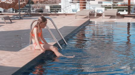 つま先 : Young girl teenager dipping legs in swimming pool water at resort. Teenager girl sitting on pool edge and splashing water by feet at sunny day on summer vacation