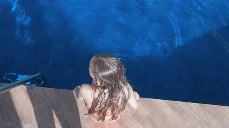 yüzme havuzu : Girl sitting on pool side swaying legs in swimming pool water outdoor overhead view. Top view girl splashing legs in blue water swimming pool in resort