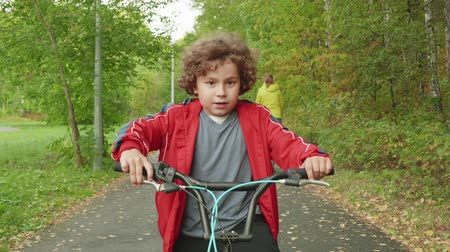boyhood : Adorable little boy with curly hair riding bicycle in park. Adorable child in red jacket sitting on bike and looking at camera outdoor. Childhood concept