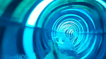 waterslide : POV shot of person riding in slide tube. Cropped shot of human legs in water riding in colorful slide tube.