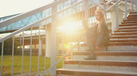 serseri : Teenager girl in black leather jacket sitting on stairs on sunflare background. Rock girl in leather jacket posing on ground crossing stairs on evening sunshine background Stok Video