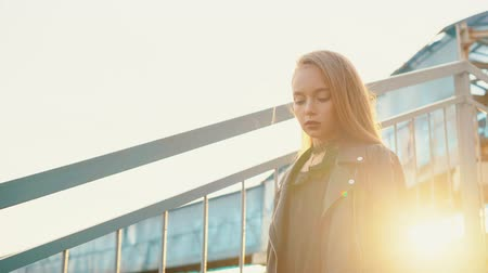 vidět : Rock girl in black leather jacket walking down stairs on golden sunlight background. Beautiful girl in punk style look posing front camera on staircase at shining sunset Dostupné videozáznamy