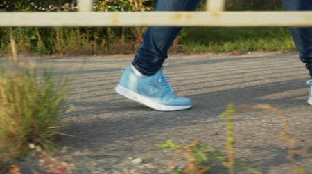 kalhoty : Child in blue sneakers walking outdoor. Low section of person in dark denim pants and blue sports shoes walking on pathway at sunny autumn day, slow motion.