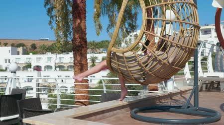 bámult : Carefree girl relaxing in hanging chair cocoon with smartphone in luxury hotel. Girl teenager swinging in cocoon chair with mobile phone at sunny terrace in resort hotel