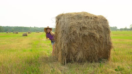 bales : Cowgirl in hat peeping out from haystack at harvesting field in village. Cowboy girl in hat and checkered shirt posing on hay stack background in countryside field Stock Footage
