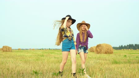 verificador : Two cowgirls walking on countryside field on haystack landscape. Young cow girls in hat and checkered shirts posing front camera. Country girl on harvesting field in village