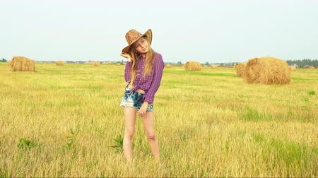 szalma : Young fashion model in cowboy hat posing on harvesting field in autumn village. Teenager girl in cowgirl look posing for camera on haystack background in countryside field