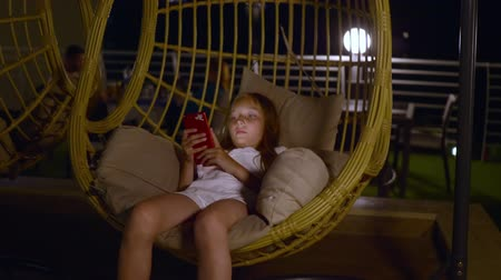 cocoon : Girl with smartphone swinging in cocoon chair. Adorable teenage girl using red mobile phone and resting in cocoon swing chair at night.