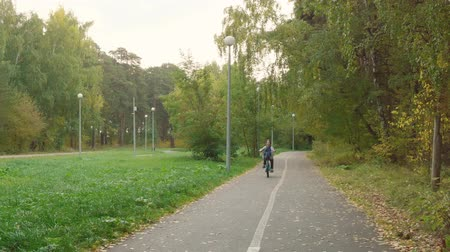 boyhood : Boy riding bicycle in park. Adorable excited teenage boy cycling bike and expressing emotions in beautiful autumn park. Stock Footage