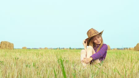 sombrero de paja : Cute girl in cowboy hat posing at photo session on rural field with haystack. Teenager girl in cowgirl look posing for camera on haystack background at harvesting field