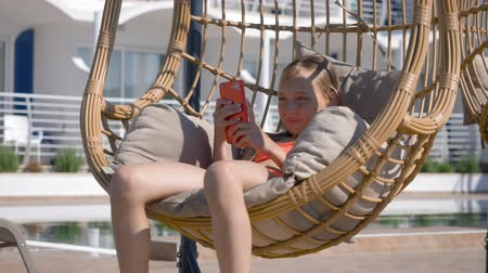 терраса : Young girl looking mobile in hanging chair cocoon in resort hotel. Girl teenager swinging in cocoon chair with using smartphone at sunny terrace in resort hotel