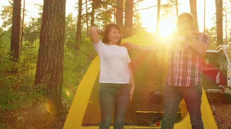 abraços : Happy couple on camping tent background. Couple in love embracing on sunshine landscape in campsite. Tourist couple meeting sunny morning in forest hike