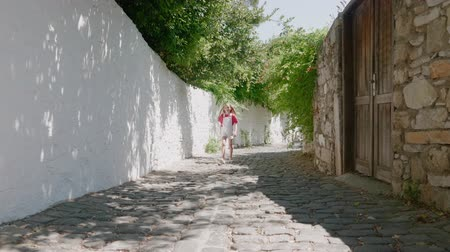 восстановлено : Girl walking by cabbles on narrow street in old city. Tourist girl walking on sunny street o rocky wall background in summer old town