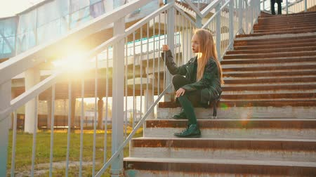 прическа : Pensive teenage girl in leather jacket sitting on stairs. Low angle view of thoughtful teenage girl in black leather jacket sitting on steps in city during sunset. Style concept
