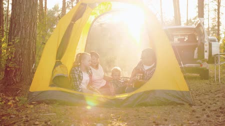 gitáros : Happy family with guitar sitting in tent in forest. Middle aged father playing guitar while mother with two children resting in yellow tent in forest during sunset. Camping concept