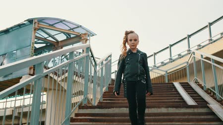 pankáč : Stylish girl walking down stairs. Low angle view of beautiful teenage girl in black leather jacket and make-up walking downstairs in urban cityscape. Dostupné videozáznamy