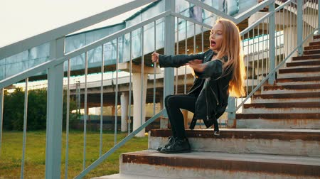pankáč : Excited stylish teenage girl posing on stairs during sunset. Low angle view of adorable girl in black leather jacket holding railing and posing on steps during sunset. Fashion concept