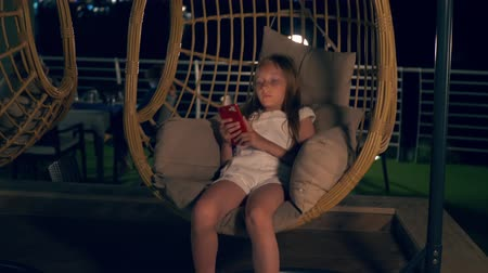 zámotek : Girl with smartphone resting in cocoon swing chair. Adorable teenage girl in white closing sitting in swing chair and using smartphone at night time